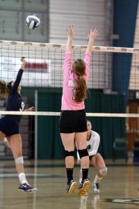 2) Mary Moore, senior, jumps to block the ball doing the Dig Pink game vs. Marietta. (Photo by Elizabeth Feudo_