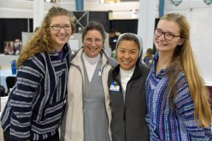Theresa Cincotta, freshman, and Desiree Pillar, freshman, smile with sisters at the vocations fair. (Photo by Elizabeth Feudo)