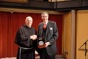 George Marlin accepts the Poverello Medal,  as chairman of Aid to the Church in Need, from Father Sean O. Sheridan, TOR. (Photo by Ulises Iniguez)