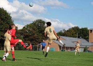 Jacob Rigaud heads a ball and score a goal against D'Youville. (Photo by Ulises Iniguez)